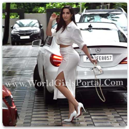 Nora Fatehi White Outfit chanel handbag cropped shirt slit skirt